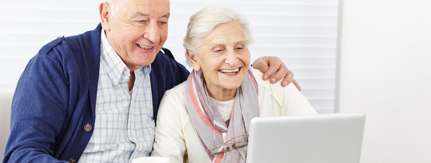 Happy senior citizen couple using social media